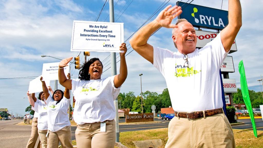 Ryla staff shaking signs for traffic at the side of the road to promote awareness