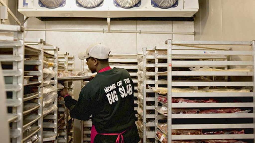 man loading a tray of bread into a rack in a walk-in refrigerator